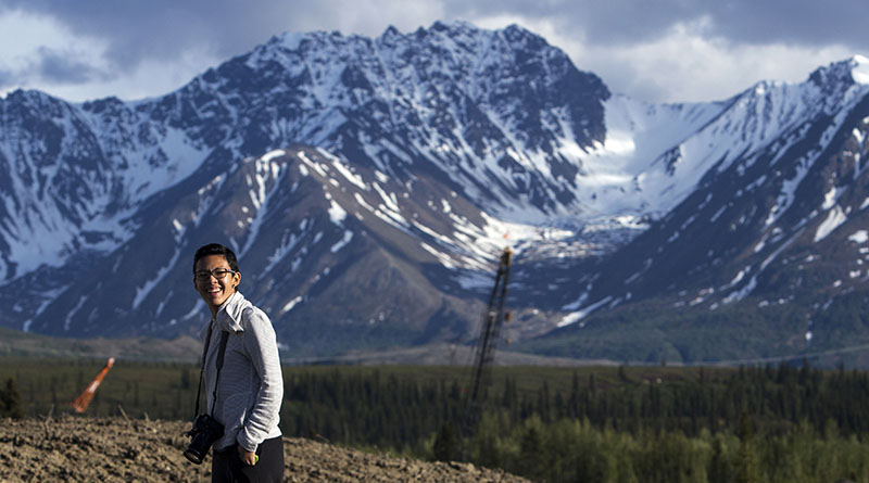 Emi Sasagawa takes a break from reporting while traveling along the George Parks Highway to Anchorage, Alaska, in June. (Photo by Sean Logan/News21)