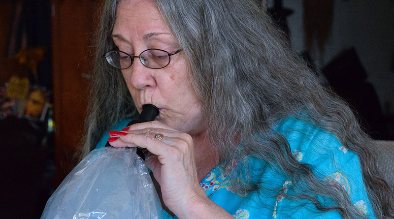 Medical marijuana patient Teri Heede takes a hit from a vaporizor in her Oahu home on June 21. Photo by Anne M. Shearer/News21