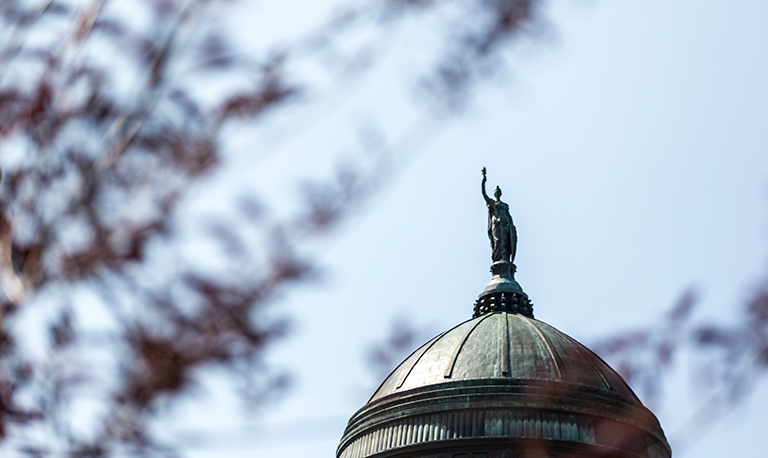 A statue tops the Montana State Capitol building, looking over the city of Helena.